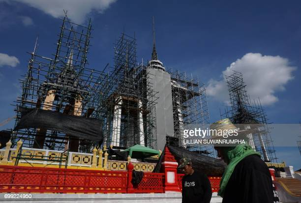 Construction workers stand in front of the funeral pyre and surrounding pavilions for the late Thai King Bhumibol Adulyadej inside Sanam Luang park...