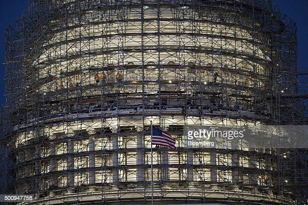 Construction workers stand in the scaffolding surrounding the dome of the US Capitol building before sunrise in Washington DC US on Friday Dec 11...