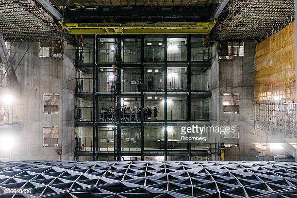 Construction workers stand inside Morpheus Melco Crown Entertainment Ltd's new hotel tower under construction at the company's City of Dreams casino...