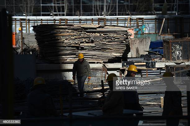Construction workers stand on a building site in Beijing on December 16 2014 Foreign investment into China accelerated in November government data...