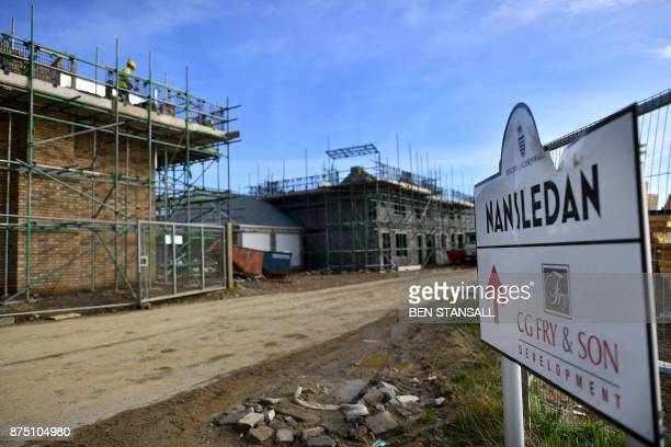 Construction workers stand on a building site in Nansledan housing development championed by Britain's Prince Charles Prince of Wales at Newquay town...