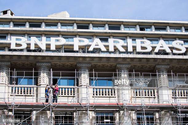 Construction workers stand on scaffolding outside a BNP Paribas SA headquarters in Paris France on Tuesday July 18 2017 BNP Paribas agreed to pay...