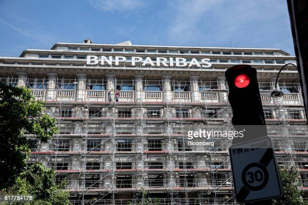 Construction workers stand on scaffolding outside the BNP Paribas SA headquarters in Paris France on Tuesday July 18 2017 BNP Paribas agreed to pay...