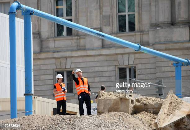 Construction workers stand on the construction site of the Berliner Schloss city palace on June 12 2013 in Berlin Germany The Berliner Schloss was...