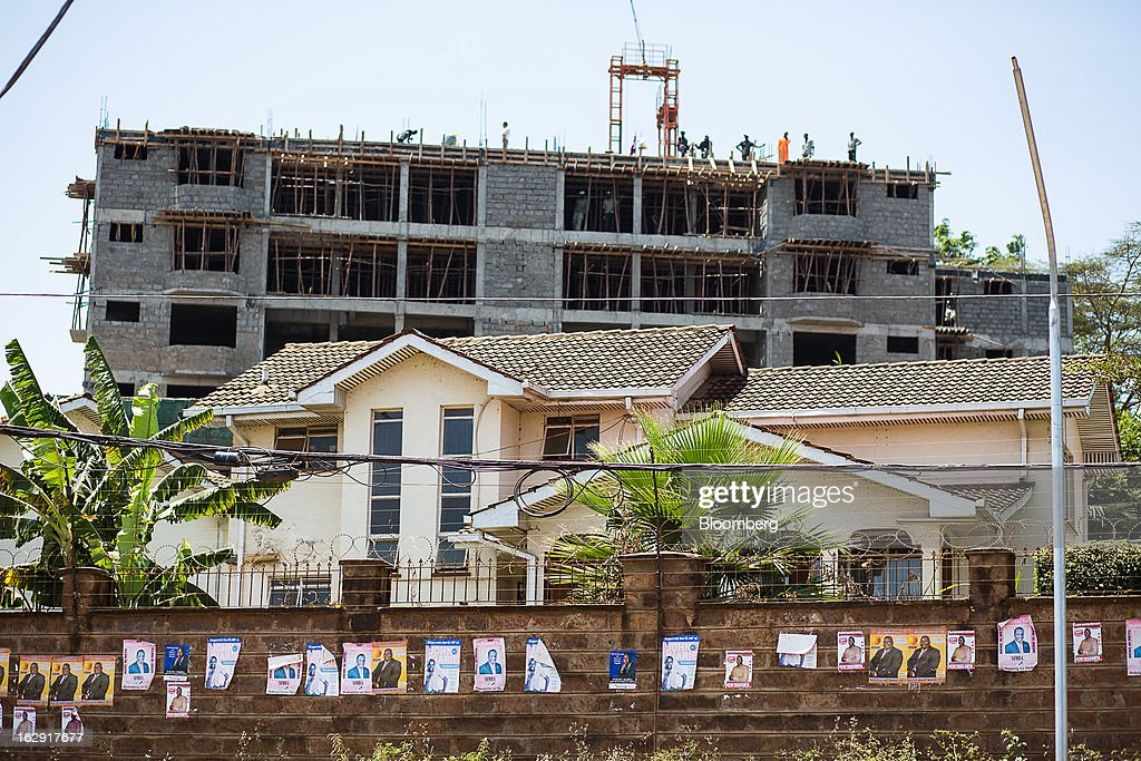 Construction workers stand on top of a new apartment block seen beyond a wall of election posters in Nairobi, Kenya, on Friday, March 1, 2013. Next week's presidential vote will be the first since disputed elections in 2007 triggered ethnic fighting in which more than 1,100 people died and another 350,000 fled their homes. Photographer: Trevor Snapp/Bloomberg via Getty Images