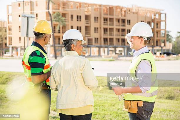 Construction workers, supervisor, engineer talk at job site.