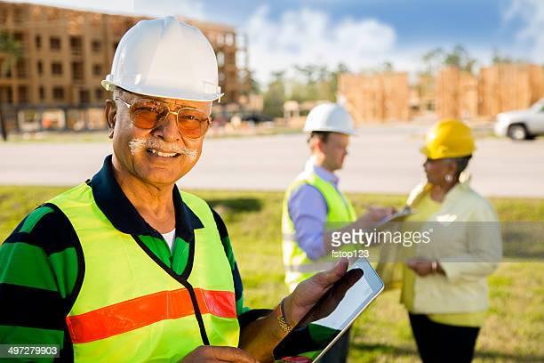 Construction workers, supervisors talk at job site. Digital tablet.