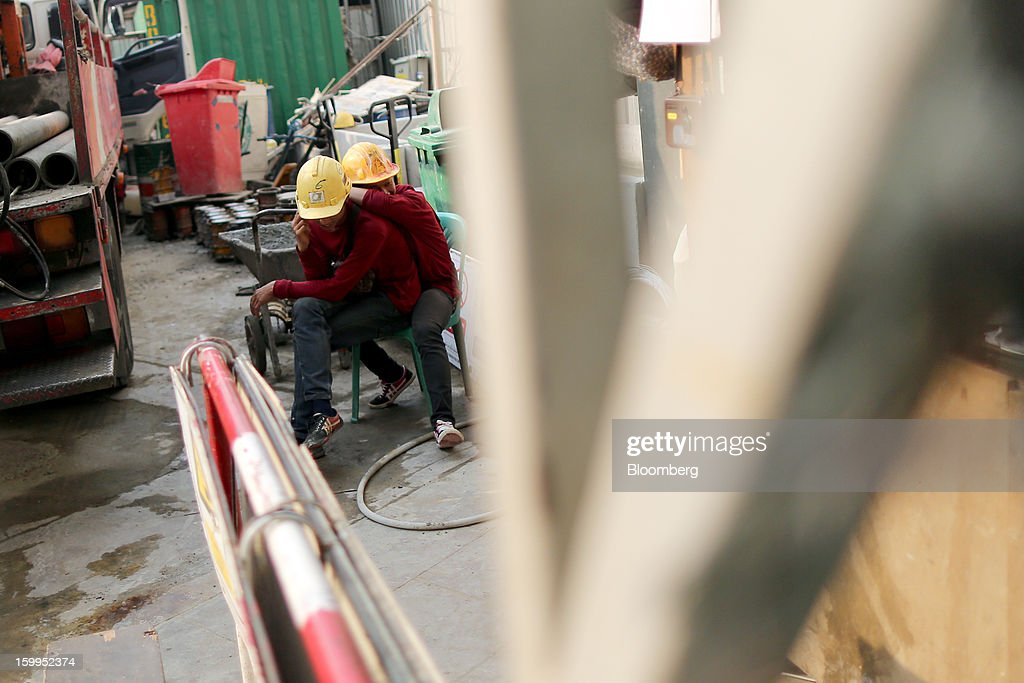 Construction workers take a break at a building site at Siam Square in Bangkok, Thailand, on Wednesday, Jan. 23, 2013. Prime Minister Yingluck Shinawatra's government last month approved a new round of increases in the daily minimum wage to 300 baht ($9.8) from the beginning of this year, after a similar raise in April in seven provinces including Bangkok. Photographer: Dario Pignatelli/Bloomberg via Getty Images