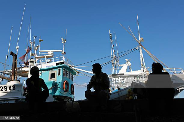 Construction workers take a break in front of moored fishing boats at Hisanohama fishing port in Iwaki Fukushima Prefecture Japan on Monday Aug 26...