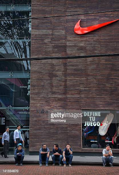 Construction workers take a break outside of a Nike Inc store in Bogota Colombia on Tuesday March 13 2012 Colombia's peso fell after the Federal...