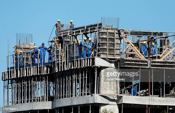 Construction workers take a break to watch a Brazil training Session ahead of their Confederations Cup 2013 match against Mexico at the Estadio...