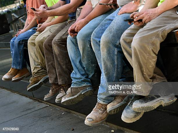Construction workers take advantage of the spring weather to sit on a wall on Park Avenue for their lunch break in New York on May 7 2015 AFP PHOTO /...