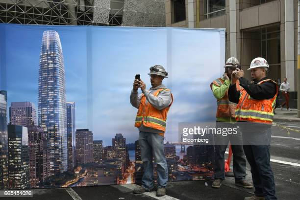 Construction workers take photographs with mobile devices during a topping off ceremony for the Salesforce Tower in San Francisco California US on...