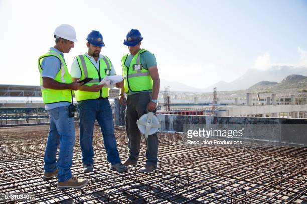 Construction workers talking on rebar at construction site