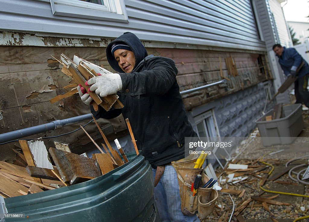 Construction workers throw away debris while repairing a home in the Staten Island borough of New York, U.S., on Wednesday, Nov. 28, 2012. Superstorm Sandy is giving the U.S. Northeast, and the rest of the country, an economic boost that may eventually surpass the loss of business it caused. Photographer: Jin Lee/Bloomberg via Getty Images