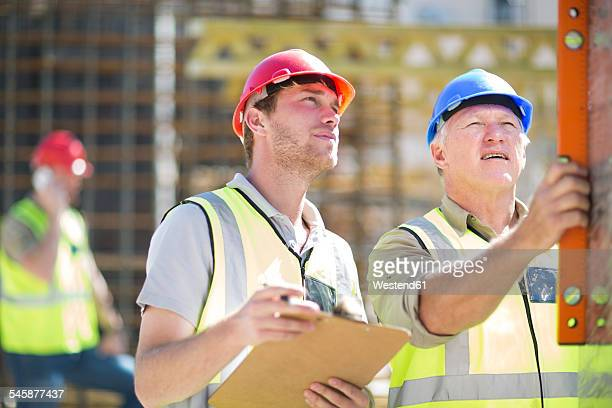 Construction workers using spirit level