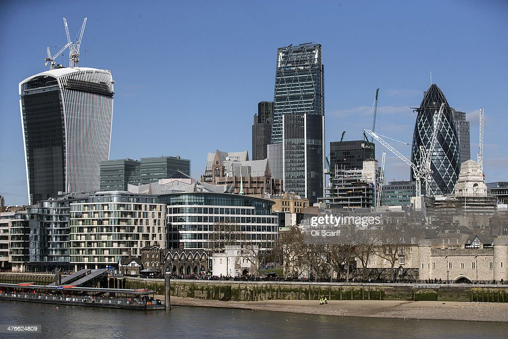 Construction workers walk along the north bank of the river Thames in front of the City of London and the Tower of London on March 4, 2014 in London, England.