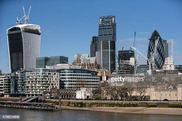 Construction workers walk along the north bank of the river Thames in front of the City of London and the Tower of London on March 4 2014 in London...