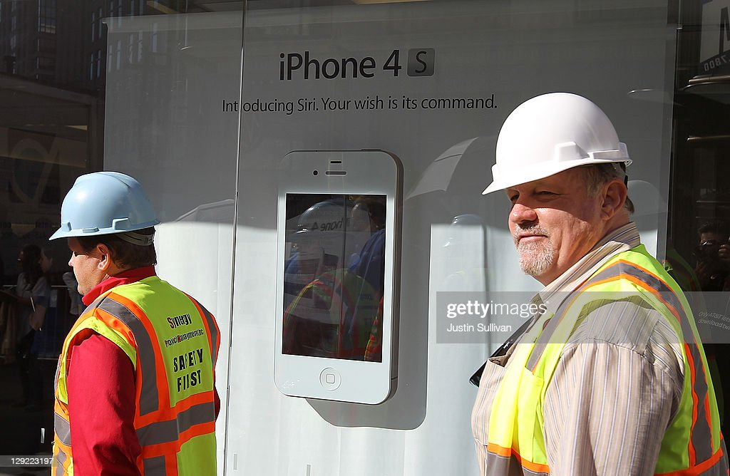 Construction workers walk by a display of the new Apple iPhone 4Gs at an Apple Store on October 14, 2011 in San Francisco, United States. The new iPhone 4Gs went on sale today and features a faster dual-core A5 chip, an 8MP camera that shoots 1080p HD video, and a voice assistant program.