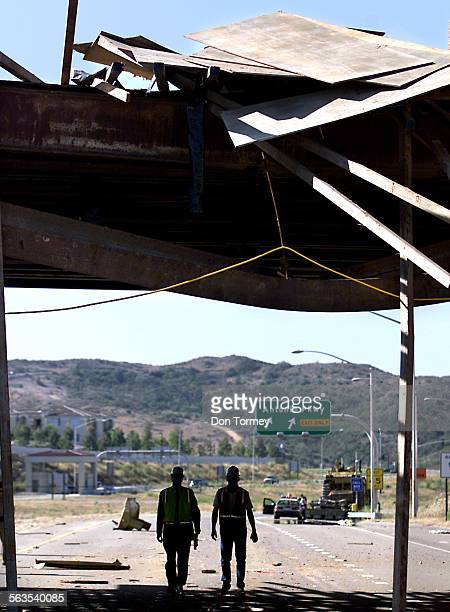 Construction workers walk near debris that was torn off a bulldozer and the bridge above after a tractor–trailer truck hauling the Caterpillar...