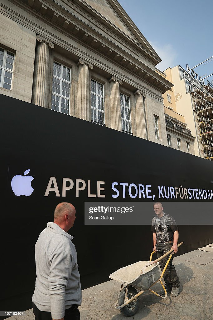 Construction workers walk past the construction site of the new Apple Store on Kurfuerstendamm avenue on April 22, 2013 in Berlin, Germany. The store is due to open in May and will the be the first Apple Store to open in the Germany capital.