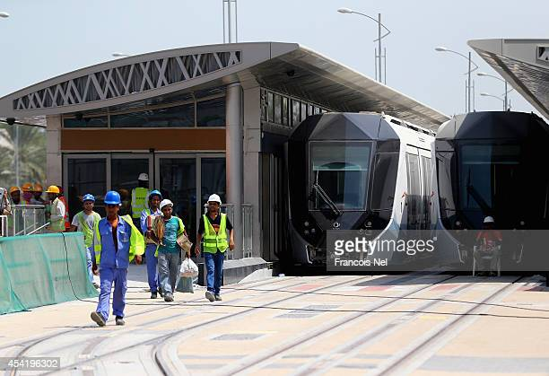 Construction workers walk past the Dubai Tram on August 26 2014 in Dubai United Arab EmiratesThe first phase of the Dubai Tram network is expected to...