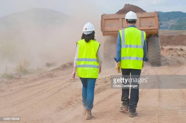 Construction workers walking behind dump truck