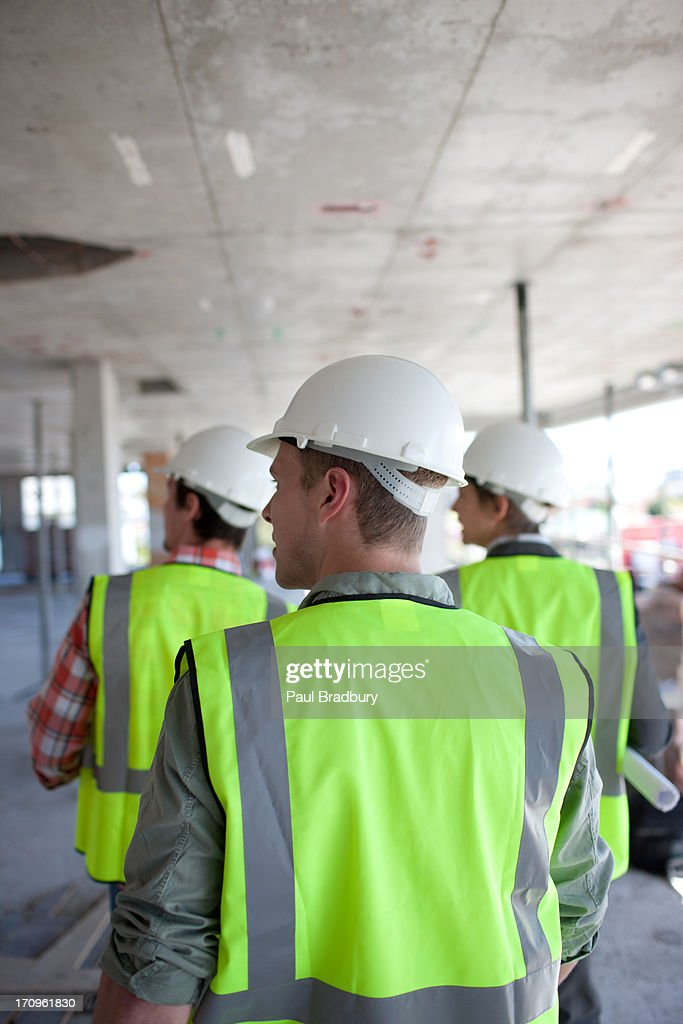 Construction workers walking on construction site : Stock Photo