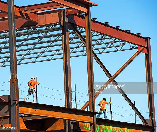 Construction workers walking on steel girders, New York City, New York, United States
