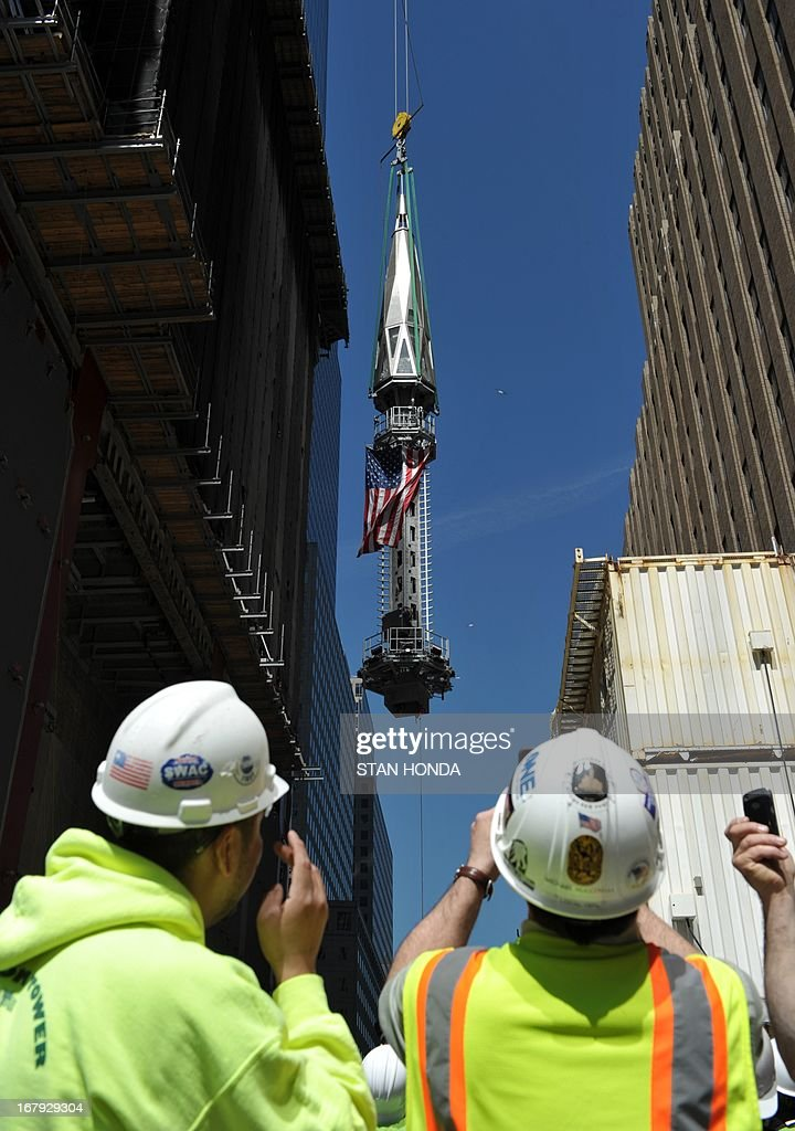 Construction workers watch as the final sections of the spire is raised to the top of One World Trade Center May 2, 2013 in New York to a temporary work platform atop the structure. Ironworkers will install the sections at a later date and when complete, One WTC will stand 1,776 feet (541 meters) high, making it the tallest building in the Western Hemisphere. AFP PHOTO/Stan HONDA