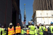 Construction workers watch as the final sections of the spire is raised to the top of One World Trade Center May 2 2013 in New York to a temporary...
