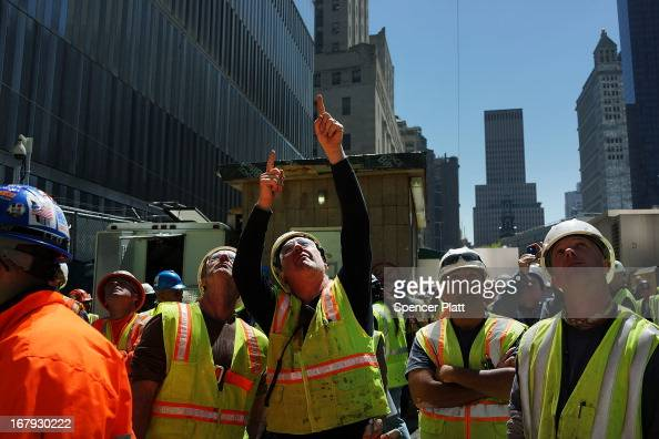 Construction workers watch as the last 75foot section of the 408foot spire is hoisted onto a temporary platform on the top of One World Trade Center...
