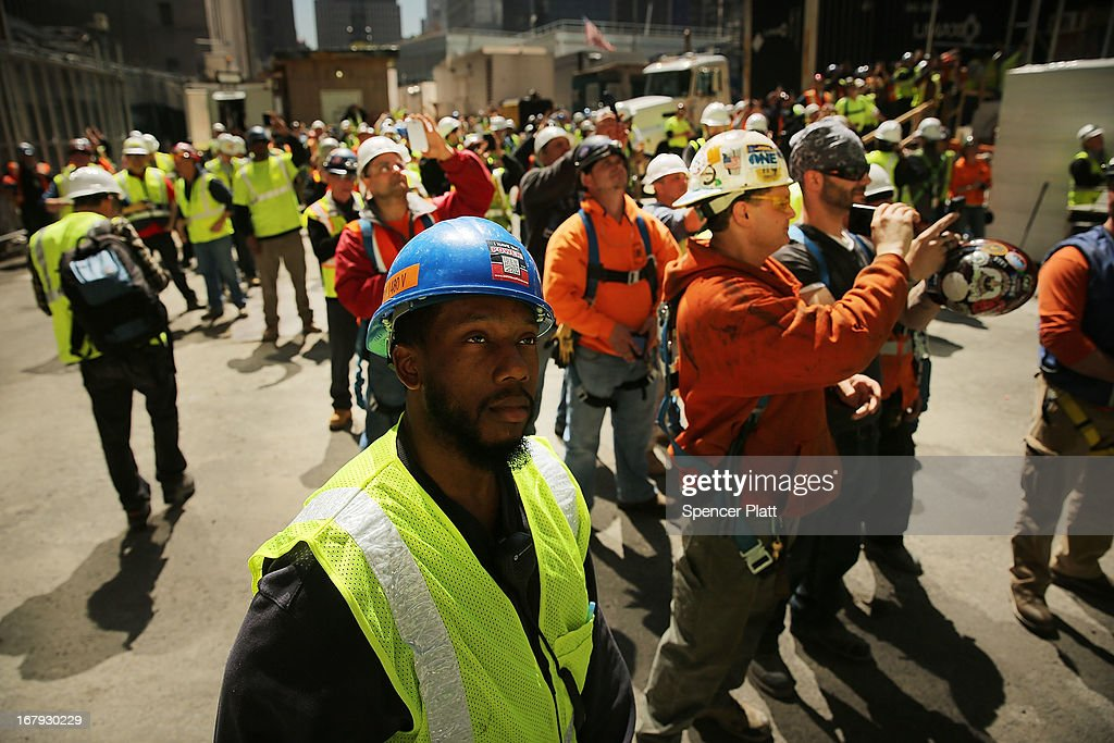 Construction workers watch as the last 75-foot section of the 408-foot spire is hoisted onto a temporary platform on the top of One World Trade Center on May 2, 2013 in New York City. When bolted into place at a later date, the spire will make One World Trade Center the tallest building in the Western Hemisphere.The raising of the spire, which comes on the second anniversary of the death of Osama bin Laden, will make One World Trade Center 1,776 feet tall. One World Trade Center is built on the site where the September 11, 2001 attacks toppled the original World Trade Center towers.