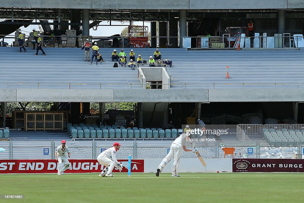 Construction workers watch the cricket game during a break during day one of the Sheffield Shield match between the Redbacks and the Warriors at Adelaide Oval on November 13, 2013 in Adelaide, Australia.