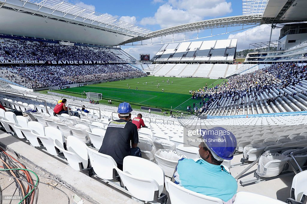 Construction workers watch the test event match of past and present Corinthians players at Arena Corinthians on May 10, 2014 in Sao Paulo, Brazil. The stadium will be used during the World Cup starting next month as Arena de Sao Paulo, hosts the opening game between Brazil and Croatia.
