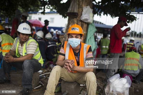 Construction workers wearing hard hats and hivis jackets sit down for a break during a shift change in Phnom Penh Cambodia on Monday Oct 24 2016...
