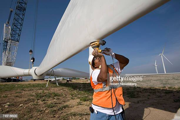Construction workers with the help of a crane sand the surface of a propeller at a tower base on the Lone Star Wind Farm on June 7 17 miles north of...