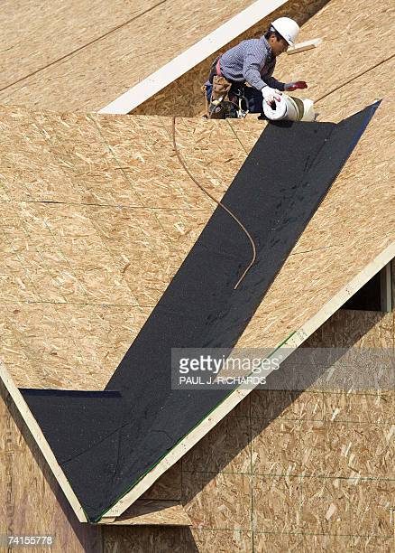 Construction workers work on the rooftop of a new home under construction in Centreville Virginia 15 May 2007 as the first layer of tar paper appears...