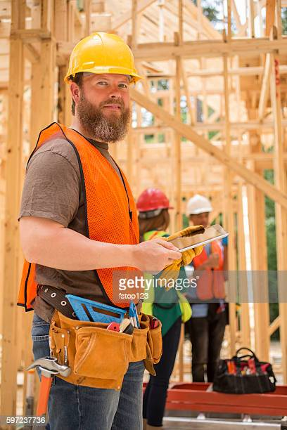 Construction workers working at job site using digital tablet.