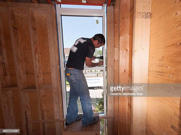 Construction workers working installing European style windows in a construction site of a private house