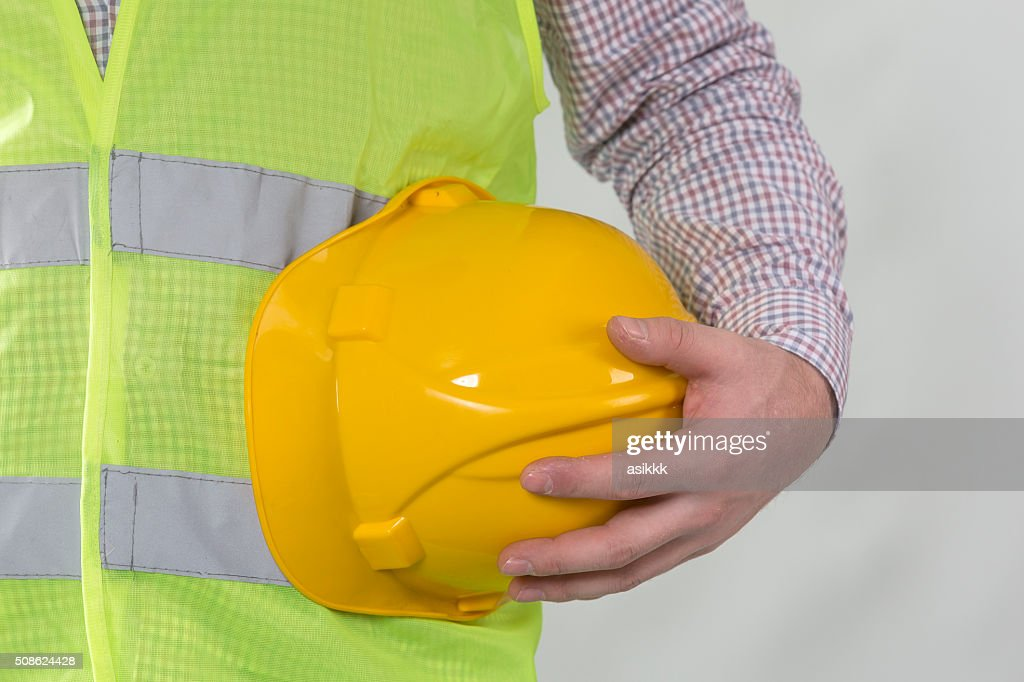Constructor hand holding yellow Safety helmet. : Stock Photo