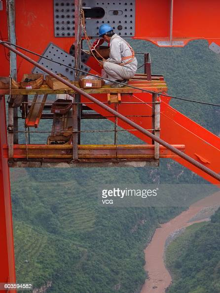 A constructor works on the Beipan River expressway bridge on September 9 2016 in Bijie Guizhou Province of China The 13414meterlong Beipan River...