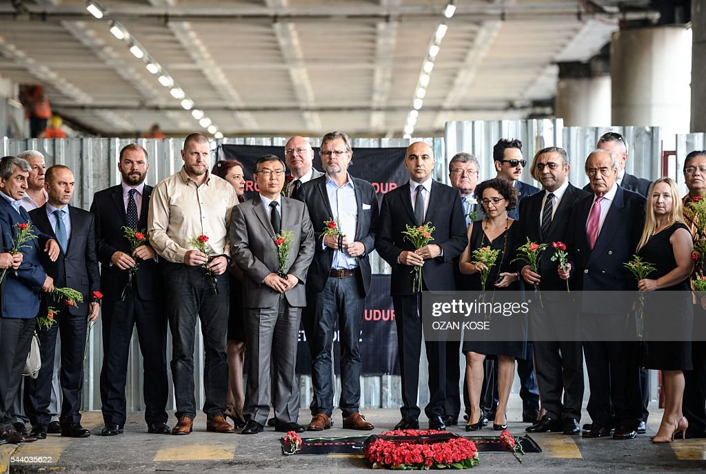 Consuls of European countries stand as they hold cloves and roses at the explosion site at Ataturk airport International terminal on July 1, 2016 three days after a suicide bombing and gun attack targeted Istanbul's Ataturk airport, killing 44 people. Although no group has yet claimed Tuesday's gun and bomb attack which killed 42 people, Ankara has pointed a finger at IS, which has been blamed for several suicide attacks around the country in the past year. / AFP / OZAN