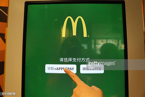 A consumer points the button of Apple Pay on a selfhelp machine at a McDonald's on February 18 2016 in Beijing China Apple CEO Tim Cook has today...