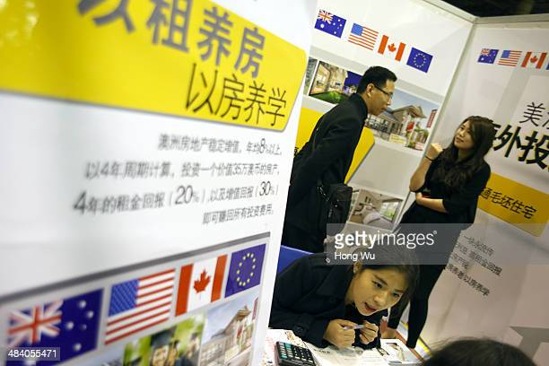 Consumer talks with a real estate salesperson about an overseas housing investment project at a real estate fair on April 11 2014 in Qingdao China...
