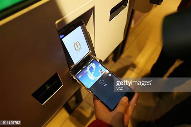 A consumer uses Apple Pay on the iPhone at a McDonald's on February 18 2016 in Beijing China Apple CEO Tim Cook has today confirmed the launch of...