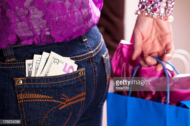 Consumerism.  Woman with money in back pocket and shopping bag
