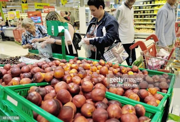 Consumers buy nectarines and cherries at the fruits section in an Auchan supermarket a branch of the French international retail group Auchan on June...