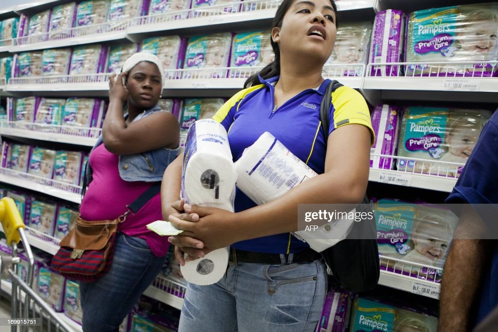 Consumers buy rationed goods during the inauguration of the state-owned Bicentenario supermarket in Caracas, on June 4, 2013. For almost a month there has been a shortage around the country of toilet paper due to a drop in its production and imports. AFP PHOTO/Leo RAMIREZ