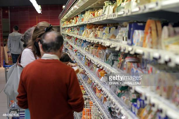 Consumers peruse the fridge shelves at a supermarket on August 18 2015 in Coutances northwestern France AFP PHOTO/CHARLY TRIBALLEAU